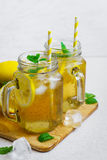Green ice tea with lemon and mint in a glass jar. Stock Photos