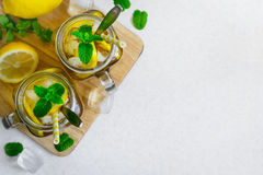 Green ice tea with lemon and mint in a glass jar. Top view with Stock Images
