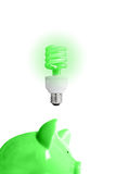Green idea. Piggy bank with energy-efficient light-bulb above (smart energy royalty free stock photography