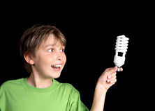 Green ideas for lighting. Horizontal closeup of a boy holding an energy efficient light globe and smiling inspirationally royalty free stock image