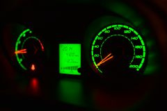 Green illuminated dials on dashboard. Close up of green illuminated digital and analog dials on automotive dashboard Royalty Free Stock Image