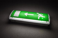 Green illuminated emergency exit sign in dark Stock Image