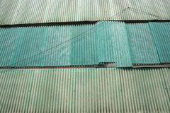 Green Industrial Abandoned Building Side With Corrugated Plastic and A Loose Hanging Wire Royalty Free Stock Images