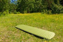 Green inflatable camping mattress on the green grass.  Stock Images