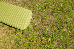 Green inflatable camping mattress on the green grass.  Royalty Free Stock Photography