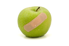 Green injured apple with plaster Stock Images