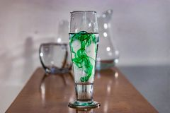 Green ink in water on table with glasswear in background. Green ink swirling in water with other empty glasses behind on table royalty free stock photo