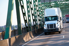 Green interstate bridge with commertial freight semi trucks on h Royalty Free Stock Image