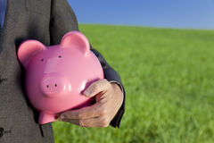 Green Investment Pink Piggy Bank. Green investment concept shot of a man in a suit holding a big pink piggy bank in a green field with a bright blue sky. Shot on