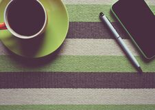 Green Iphone 5c Next to Coffee Mug Stock Photography