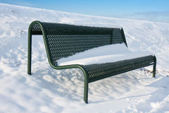 Green iron bench covered by snow. In wintertime royalty free stock photos
