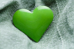 Green iron heart shape on cloth Royalty Free Stock Images