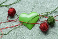 Green iron heart shape and three clew balls Stock Photography