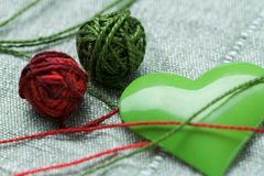 Green iron heart shape and two clew balls Royalty Free Stock Photos