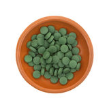 Green iron supplement tablets in a small bowl Royalty Free Stock Image