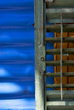 Green iron venetian blind and a blue metal wall Royalty Free Stock Images