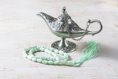 Green islamic prayer beads, dates and silver aladdin`s lamp on wooden background. Ramadan concept. Stock Photo