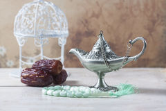 Green islamic prayer beads, dates and silver aladdin`s lamp on wooden background. Ramadan concept. Selective focus Royalty Free Stock Photos