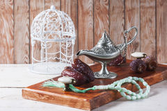 Green islamic prayer beads, dates and silver aladdin`s lamp on wooden background. Ramadan concept. Selective focus Stock Photography