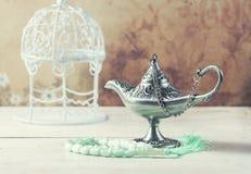 Green islamic prayer beads and silver aladdin`s lamp on wooden background. Ramadan concept. Stock Photos