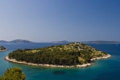 Green island in the aquamarine sea Stock Photo