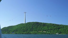 A green island in the bue sea with aerial tramway pylon and moving cable cars.