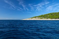 Geen island on blue sea water and sky. Green island covered with aleppo pine trees, clear, blue, rippled sea water and blue sky Stock Photography