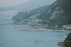 Green Island With Curved Bridge Near Body of Water Stock Photos