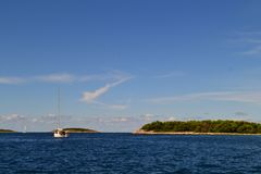 Green islands in the azure sea. A boat in the distance and blue sky. Croatia. stock photos