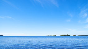 Green islands in blue water and sky Stock Image