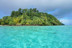 Green islet with turquoise water Huahine island Royalty Free Stock Image