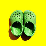 Green isolated shoes on yellow background. Green isolated children shoes with shadow on yellow background crocs Royalty Free Stock Photography