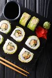 Green japanese roll with avocado, tamago omelette, sesame and cucumber closeup on a plate. Vertical top view stock image