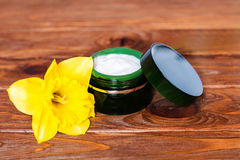 Green jar of cream with cover and narcissus on wooden back ground Stock Photography