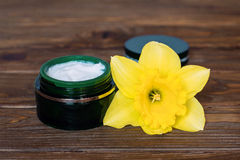 Green jar of cream and narcissus on wooden back ground Royalty Free Stock Image