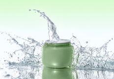 Green jar of moisturizing cream stays on the water background with  water splashes around Stock Photography