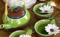 Green Jasmine tea pot with lime and flowers Royalty Free Stock Photo