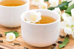 Green jasmine tea in white cups, selective focus Stock Photos