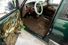 A green jeep with a beige interior is being serviced by an auto service, the skin on the open side door is removed, electrical stock photos