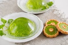 Green jelly with mint leaves in glass on a linen napkin on a white background. Green jelly with mint leaves in glass on wooden background. Juice with ice in Royalty Free Stock Images