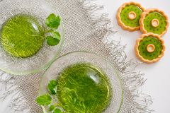 Green jelly with mint leaves in glass on a linen napkin on a white background. Green jelly with mint leaves in glass on wooden background. Juice with ice in Stock Photo