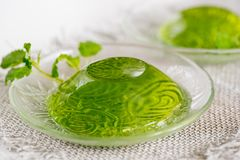 Green jelly with mint leaves in glass on a linen napkin on a white background. Green jelly with mint leaves in glass on wooden background. Juice with ice in Stock Image