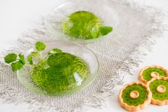 Green jelly with mint leaves in glass on a linen napkin on a white background. Green jelly with mint leaves in glass on wooden background. Juice with ice in Royalty Free Stock Photography