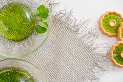 Green jelly with mint leaves in glass on a linen napkin on a white background. Green jelly with mint leaves in glass on wooden background. Juice with ice in Royalty Free Stock Photo