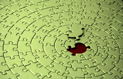 Green jigsaw with the missing piece laying above the space. Shallow DOF, focus is on the missing piece - adobe RGB Royalty Free Stock Photography