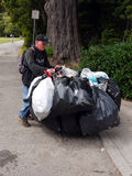 Green Jobs. Homeless person with a huge hoard of aluminium cans in garbage bags collected for recycle. He is pushing his cart in the Golden Gate Park in San Stock Photos