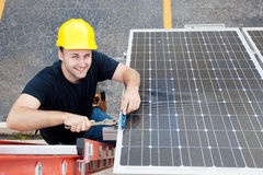 Green Jobs - Renewable Resources. Electrician installing solar panels on the roof of a building royalty free stock image