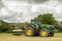 Green john deere 7820 pulling a plough Stock Image