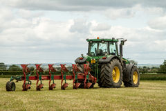 Green john deere 7820 pulling a plough Stock Images