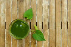 A green juice glass & leaves on wooden table in the garden. A green juice glass & leaves on wooden table in the garden in daylight Royalty Free Stock Images